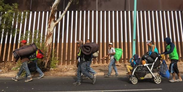 Migrantes centro-americanos caminham nesta terça-feira em Mexicali (México) ao lado da cerca na fronteira com os EUA. JUAN BARAK EFE